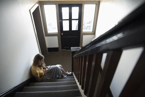 Young woman using smart phone on apartment stairs - HEROF12460