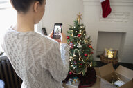 Young woman with camera phone photographing apartment Christmas tree - HEROF12469