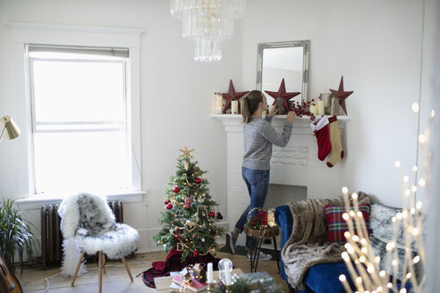 Young woman decorating living room for Christmas - HEROF12484