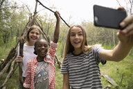 Tween girl friends taking selfie, making teepee in woods - HEROF12499