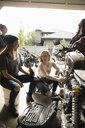 Young women friends repairing motorcycle in garage - HEROF12511