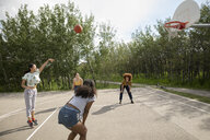 Teenage girl friends playing basketball at park basketball court - HEROF12529