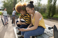 Teenage girl friends using smart phone, hanging out in park - HEROF12532