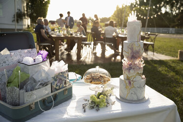 Tiered wedding cake, gifts and flowers on patio table - HEROF12538