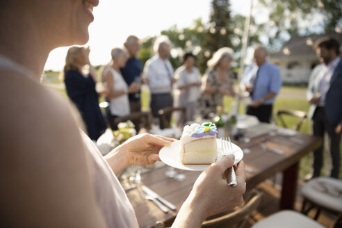 Woman eating cake, celebrating at sunny garden party with friends - HEROF12541