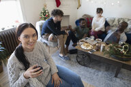 Portrait smiling young woman drinking wine, hanging out with friends in Christmas living room - HEROF12547