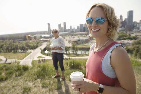 Portrait smiling woman drinking coffee and walking in sunny urban park with mother - HEROF12583