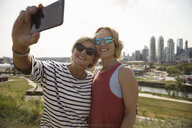 Smiling mother and daughter taking selfie in sunny urban park - HEROF12586