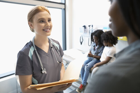 Smiling female nurse discussing medical record with mother in clinic exam room - HEROF12601