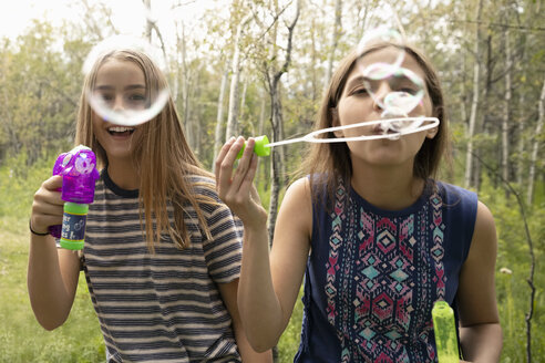 Portrait playful tween girl friends playing with bubble wands - HEROF12616