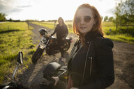 Portrait confident, cool woman with motorcycle on sunny rural road - HEROF12631