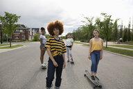 Portrait confident, cool teenage girls skateboarding on neighborhood street - HEROF12643