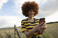Smiling teenage girl using smart phone in rural field - HEROF12646