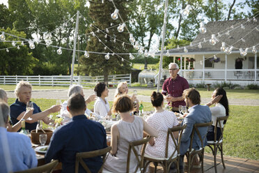 Senior man giving celebratory toast at garden party table - HEROF12655