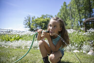 Smiling girl drinking from hose in sunny rural garden - HEROF12664