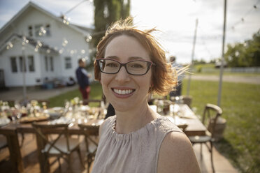 Portrait smiling, confident woman at wedding reception in sunny rural garden - HEROF12667