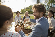 Smiling man serving salad at wedding reception lunch at sunny rural table - HEROF12673