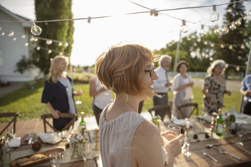 Smiling woman drinking wine at sunny rural garden party - HEROF12676