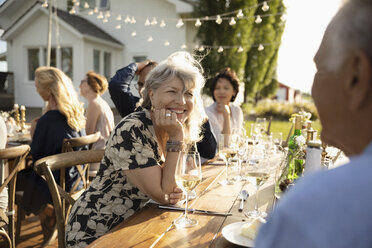 Smiling woman drinking wine, talking with man at sunny garden party - HEROF12679