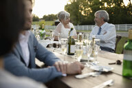 Senior bride and groom talking at wedding reception table in rural garden - HEROF12685