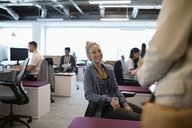 Smiling businesswoman talking with colleague in open plan office - HEROF12694