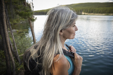 Serene mature woman hiking at forest lakeside - HEROF12700