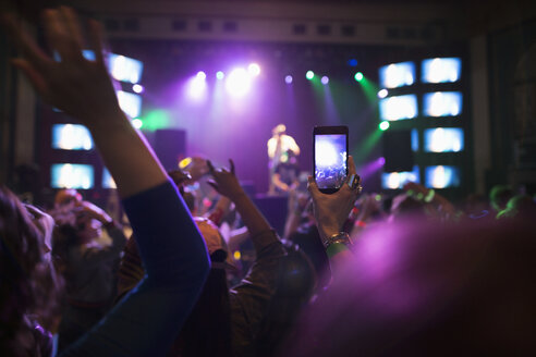 Crowd watching musician perform on nightclub stage, videoing with camera phone - HEROF12787