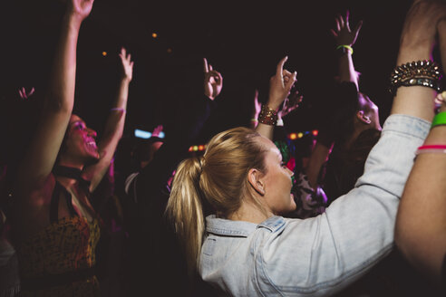 Crowd dancing and cheering at music concert in nightclub - HEROF12814