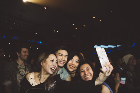 Confident, enthusiastic young millennial friends taking selfie with camera phone at nightclub - HEROF12823