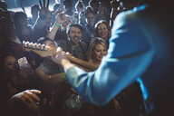 Crowd cheering for rockabilly musician playing electric guitar on stage at music concert - HEROF12850