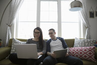 Couple using laptop and digital tablet on living room sofa - HEROF12889