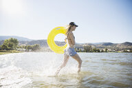 Smiling young woman in bikini running with inner tube in sunny summer lake - HEROF12910
