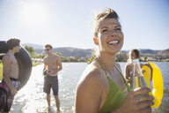 Smiling young woman drinking bottled water at sunny summer lake with friends - HEROF12913
