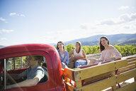 Vintner driving women in truck bed enjoying sunny vineyard tour - HEROF12979