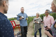 Vintner explaining red wine bottle to couples wine tasting in vineyard - HEROF12994