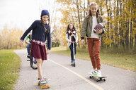 Tween girls skateboarding on autumn park path - HEROF13027