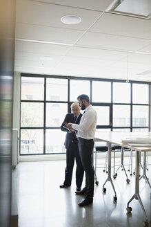 Businessmen using digital tablet in conference room - HEROF13123
