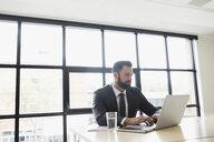 Brunette businessman with beard using laptop in office - HEROF13129