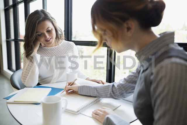 Businesswomen brainstorming at office table - HEROF13144
