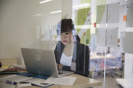 Businesswoman working at laptop in office - HEROF13153