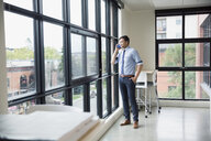 Businessman talking on cell phone at office window - HEROF13183