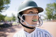 Close up middle school girl softball player with mouth guard wearing batting helmet - HEROF13195