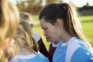 Attentive middle school girl soccer player listening in huddle - HEROF13198