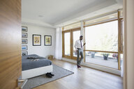 Businessman texting with cell phone at bedroom window - HEROF13204