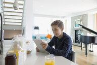 Boy using digital tablet at breakfast in morning kitchen - HEROF13213