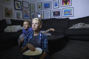 Brother and sister eating popcorn watching movie in dark living room - HEROF13222