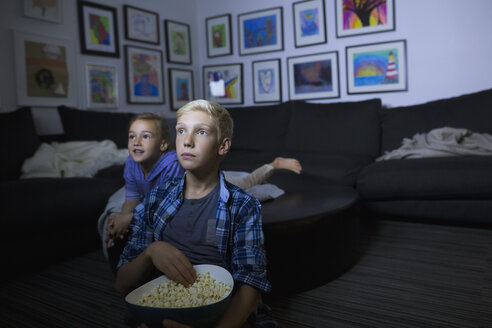 Brother and sister eating popcorn watching movie in dark living room - HEROF13222