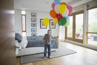 Boy holding multicolor balloons looking up in bedroom - HEROF13231