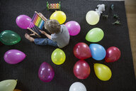 Boy playing with abacus in living room with multicolor balloons - HEROF13234