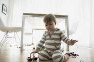 Baby boy playing with toys on dining room floor - HEROF13243